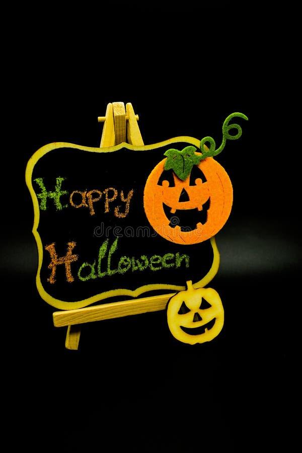 Il messaggio felice di Halloween scrive su una lavagna con le zucche Isolato su priorità bassa nera fotografia stock