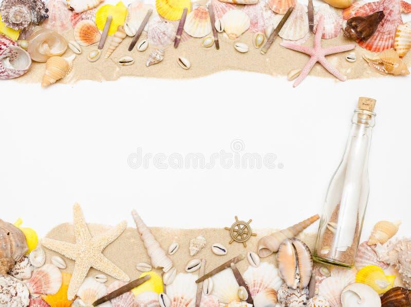 Il messaggio in una bottiglia di vetro si trova sulla spiaggia di sabbia con le conchiglie e le stelle marine immagini stock libere da diritti