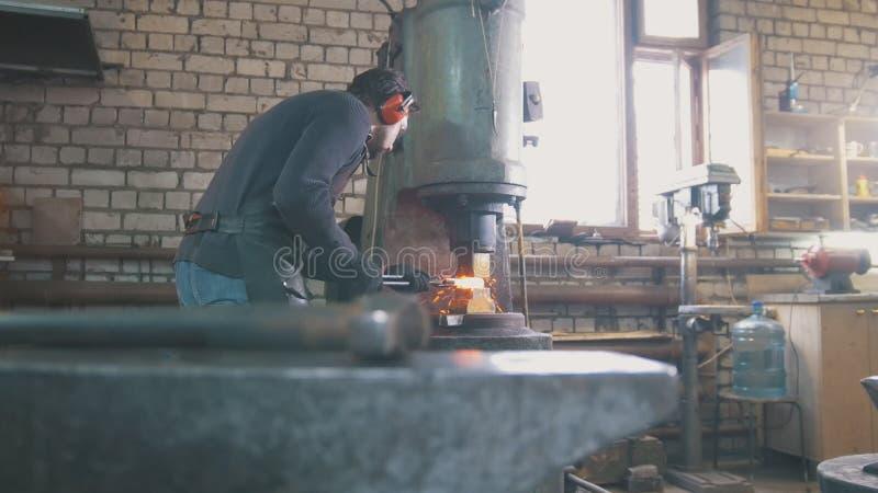 Il metallo fuso è elaborato sotto pressione nelle mani di un fabbro, grandangolari fotografia stock