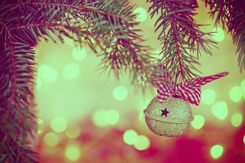 Il metallo Jingle Bell sul fondo di Natale macchia la luce fotografia stock libera da diritti