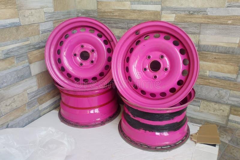 Il metallo usato ha timbrato gli orli per le automobili Ruote d'acciaio rosa su ordine sui precedenti della parete di pietra fotografie stock libere da diritti