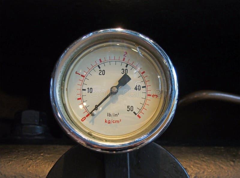 Il metro industriale di pressione del metallo rotondo ha montato su un tubo contro un fondo nero fotografia stock libera da diritti
