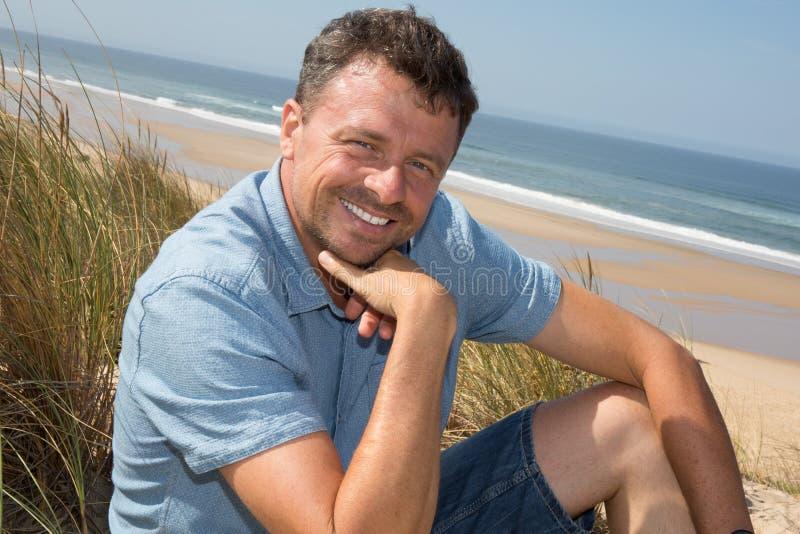 Il mezzo adorabile ed attraente ha invecchiato l'uomo che si siede sulla spiaggia immagine stock libera da diritti