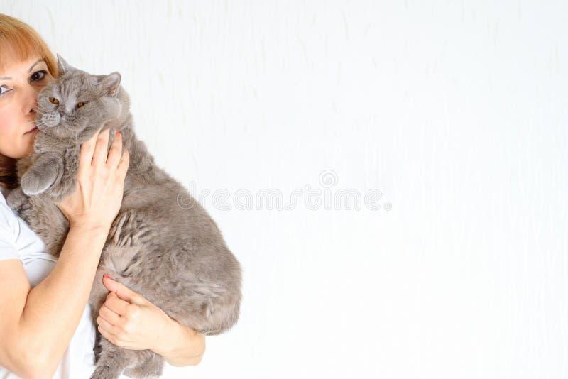 Il mezzo attraente del ritratto ha invecchiato la donna con il gatto immagine stock
