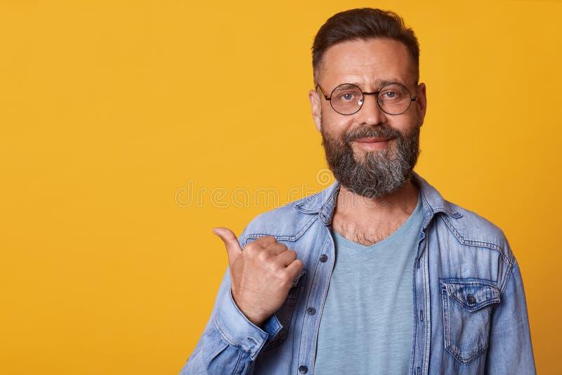 Il mezzo bello ottimista felice ha invecchiato maschio con la barba che indica da parte con il pollice e che esamina la macchina  immagine stock libera da diritti