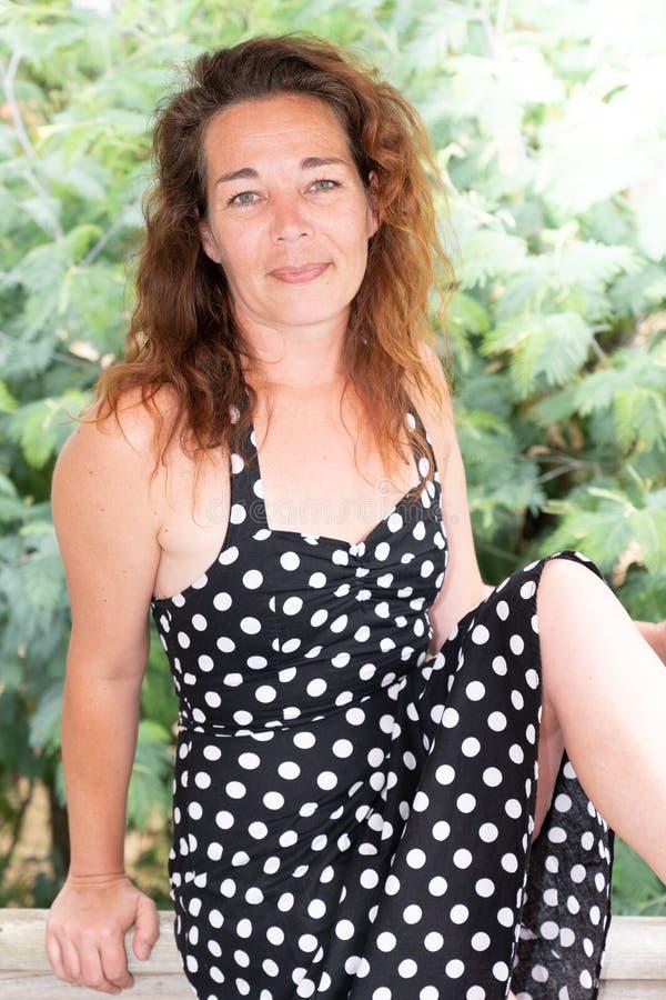 Il mezzo della donna ha invecchiato la seduta nel campo di erba in campagna fotografia stock