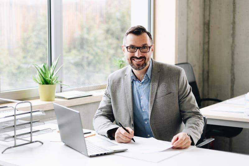Il mezzo felice ha invecchiato l'uomo d'affari bello nel funzionamento della camicia sul computer portatile in ufficio immagine stock libera da diritti