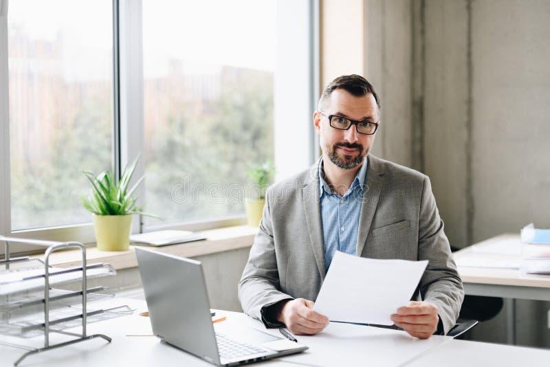 Il mezzo felice ha invecchiato l'uomo d'affari bello nel funzionamento della camicia sul computer portatile in ufficio fotografie stock libere da diritti
