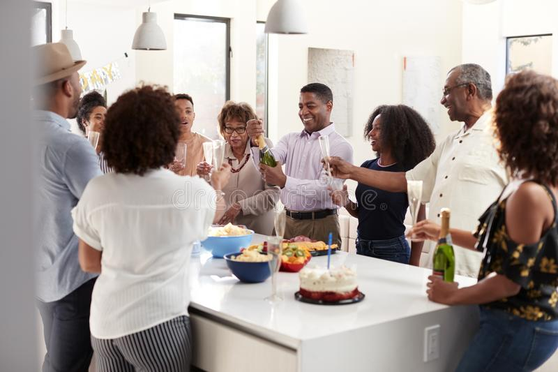 Il mezzo ha invecchiato il champagne di versamento dell'uomo afroamericano per celebrare a casa con la sua famiglia di tre genera fotografie stock libere da diritti