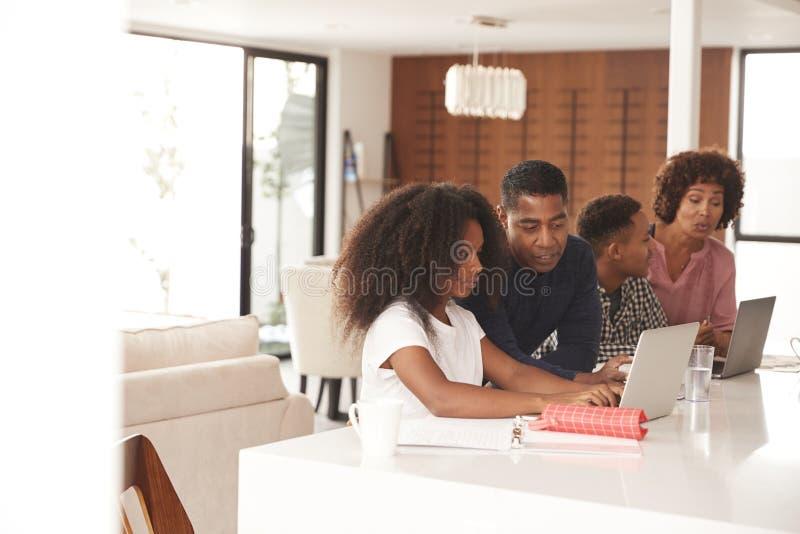 Il mezzo ha invecchiato i genitori afroamericani che aiutano i loro bambini adolescenti a fare il compito facendo uso dei compute immagine stock libera da diritti