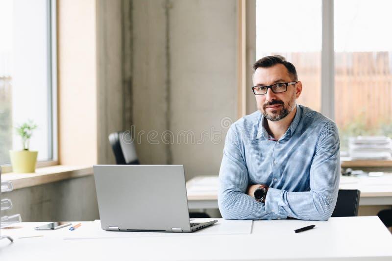 Il mezzo ha invecchiato l'uomo bello nel funzionamento della camicia sul computer portatile in ufficio fotografie stock