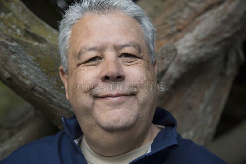 Il mezzo ha invecchiato l'uomo che sorride in ritratto all'aperto dentro per immagini stock