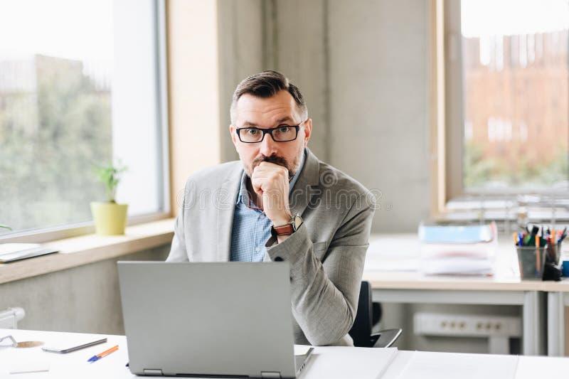 Il mezzo ha invecchiato l'uomo d'affari bello che lavora al computer portatile in ufficio fotografia stock libera da diritti