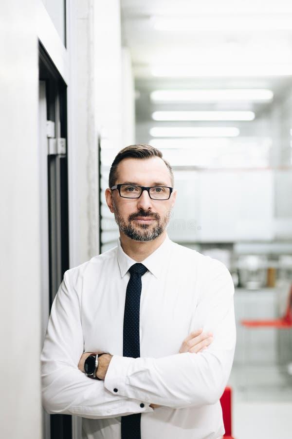 Il mezzo ha invecchiato l'uomo d'affari bello del responsabile in camicia bianca all'ufficio immagine stock