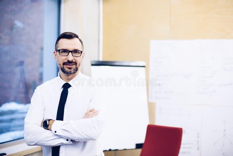 Il mezzo ha invecchiato l'uomo d'affari bello del responsabile in camicia bianca all'ufficio fotografia stock