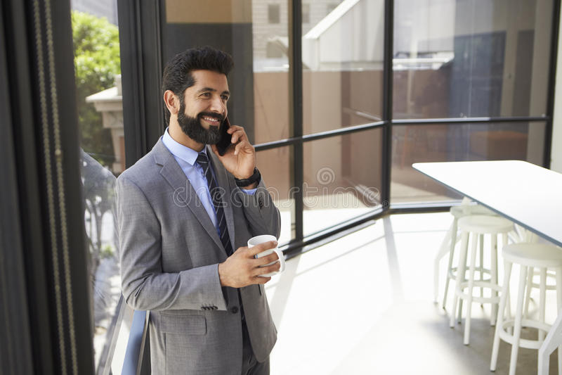 Il mezzo ha invecchiato l'uomo d'affari ispano facendo uso del telefono e tazza di tenuta fotografia stock libera da diritti