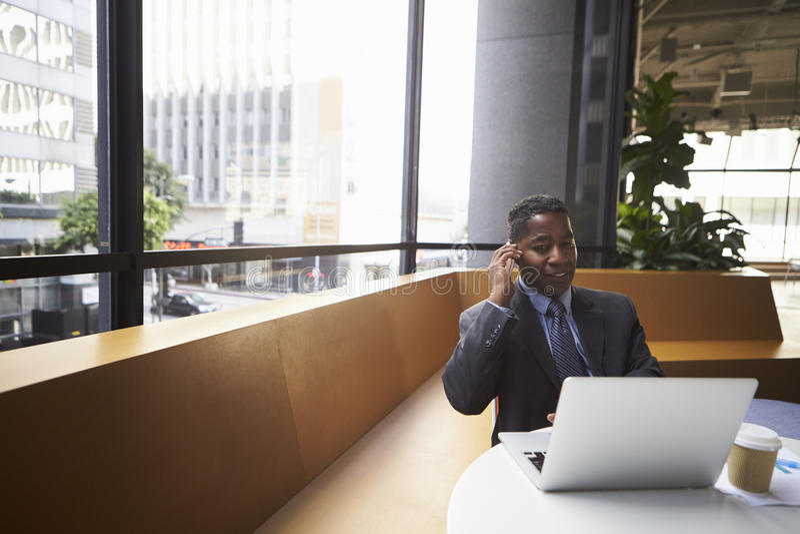 Il mezzo ha invecchiato l'uomo d'affari nero facendo uso del telefono in un ufficio moderno fotografia stock libera da diritti