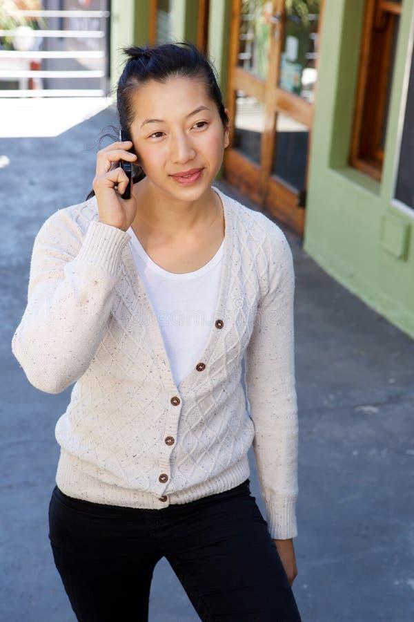 Il mezzo ha invecchiato la camminata della donna esterna e la conversazione sul telefono cellulare immagini stock