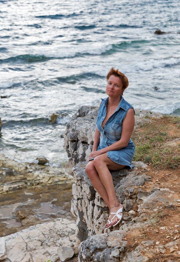 Il mezzo ha invecchiato la donna abbronzata caucasian sulla spiaggia rocciosa del mare immagini stock