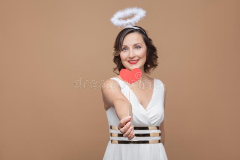Il mezzo ha invecchiato la donna castana di angelo in vestito bianco con nimbus sulla t fotografia stock libera da diritti