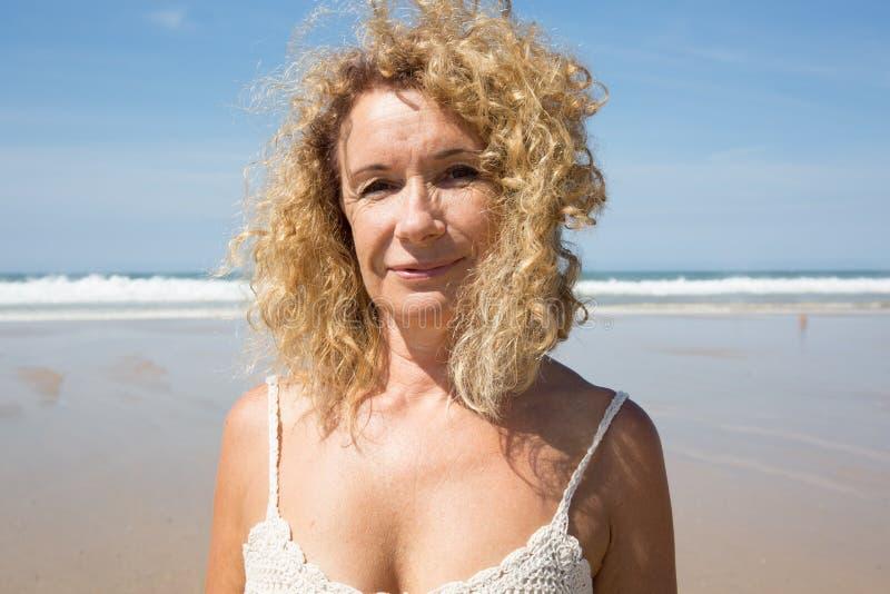 Il mezzo ha invecchiato la donna che riposa alla spiaggia vicino al mare fotografia stock