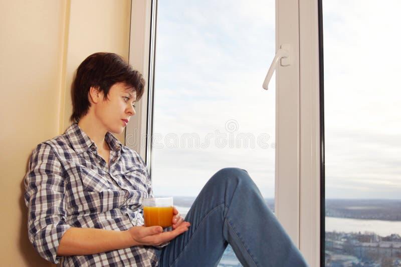 Il mezzo ha invecchiato la donna che si siede sul davanzale con un vetro di succo fotografia stock