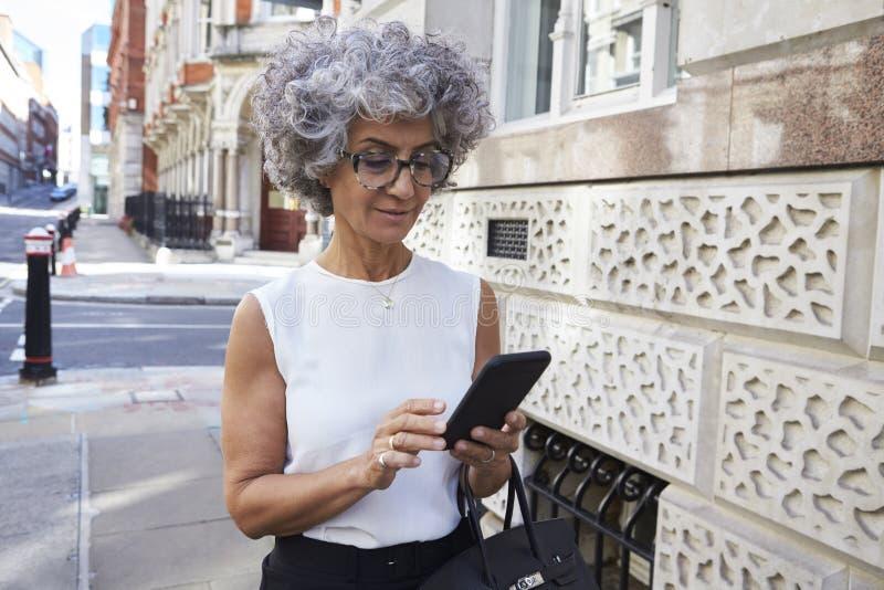 Il mezzo ha invecchiato la donna che utilizza lo smartphone nella via della città fotografie stock