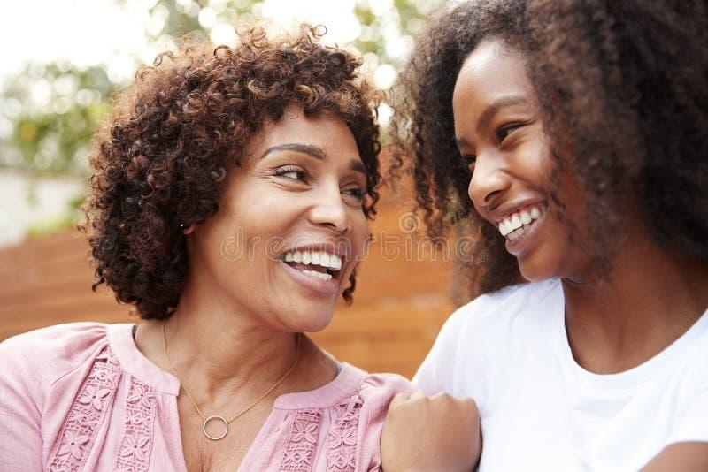 Il mezzo ha invecchiato la mummia afroamericana e la figlia teenager che sorridono ad a vicenda immagini stock libere da diritti