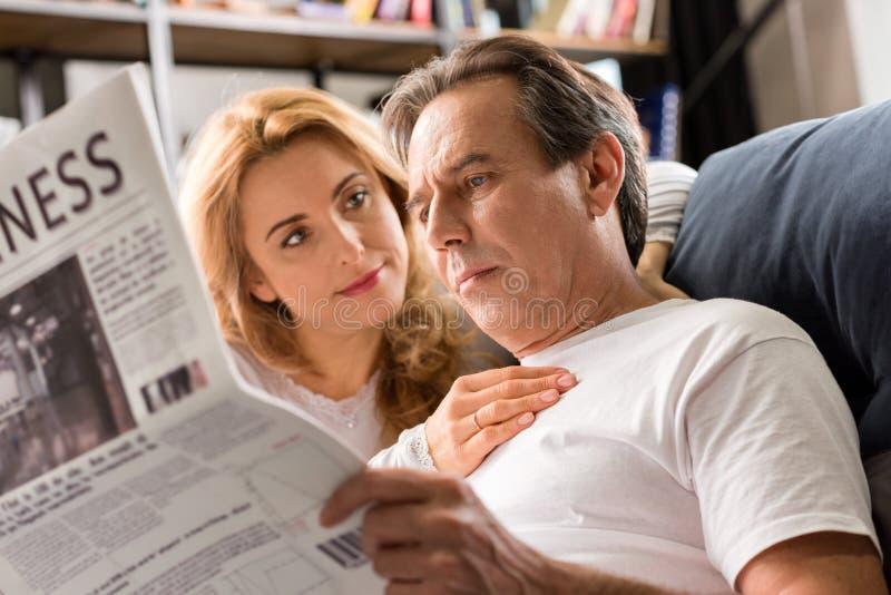 Il mezzo ha invecchiato le coppie che si siedono sul letto, giornale della lettura dell'uomo a casa fotografia stock libera da diritti