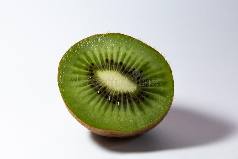 Il mezzo kiwi verde succoso si trova su un fondo bianco fotografia stock libera da diritti