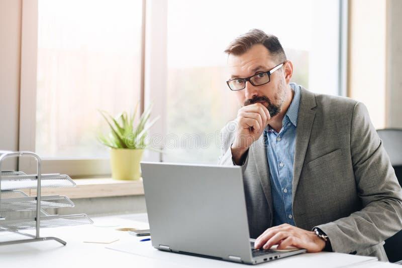 Il mezzo premuroso ha invecchiato l'uomo d'affari bello nel funzionamento della camicia sul computer portatile in ufficio immagine stock libera da diritti