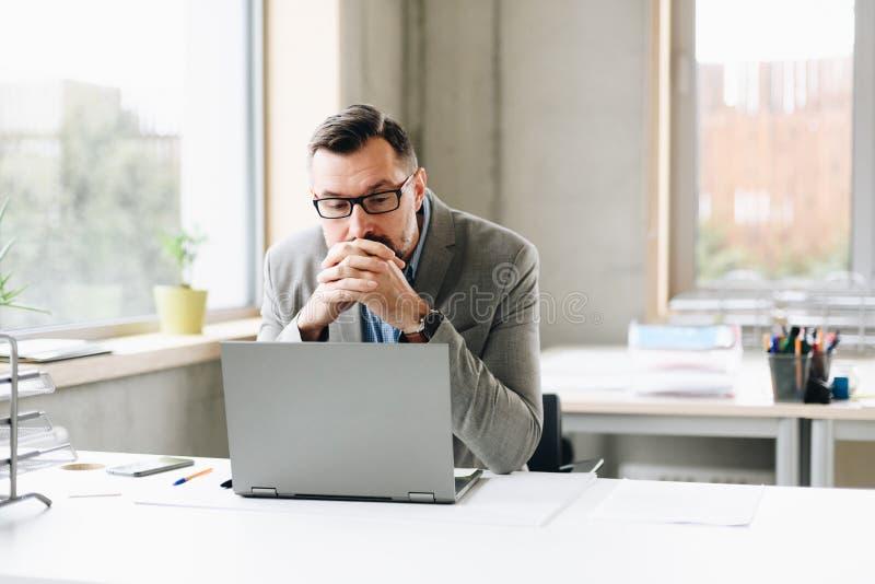 Il mezzo premuroso ha invecchiato l'uomo d'affari bello nel funzionamento della camicia sul computer portatile in ufficio immagine stock