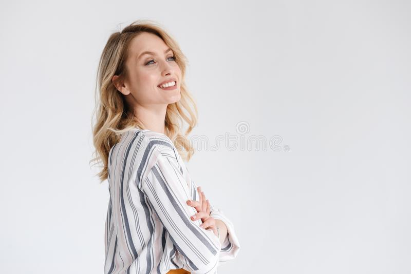 Il mezzo ritratto di giro di giovane abbigliamento casual d'uso sorridente della donna che osserva da parte il copyspace con le a immagine stock libera da diritti