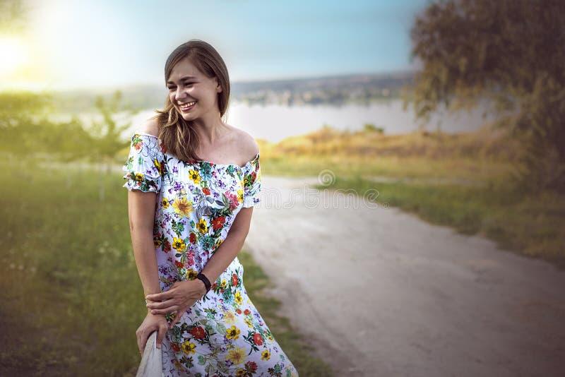 Il mezzo ritratto di lunghezza della donna positiva affascinante si è vestito nel sorridere felice del vestito bianco lungo dall' fotografia stock