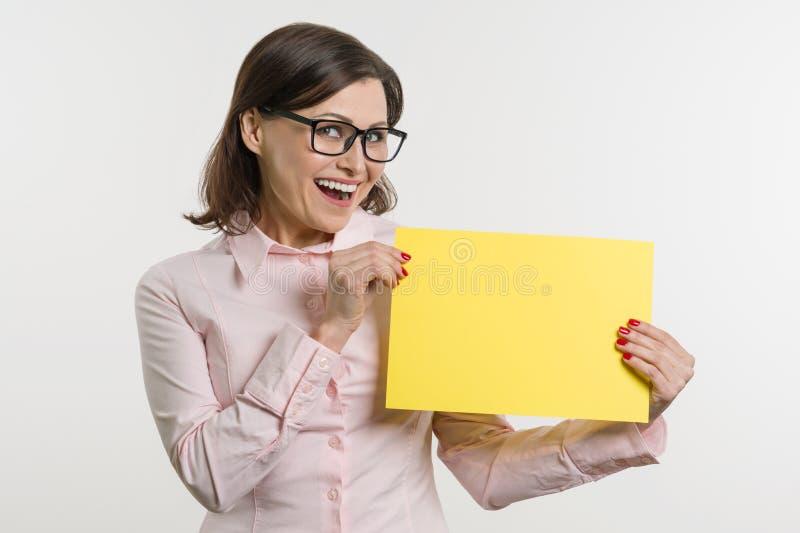 Il mezzo sorridente ha invecchiato la donna con il foglio di carta giallo immagine stock libera da diritti