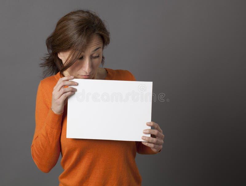 Il mezzo stupito ha invecchiato la donna che esamina giù il pannello bianco spaventoso immagine stock