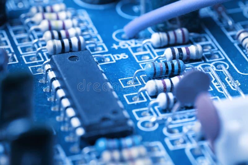 Il microchip, condensatori, resistenze su un computer blu imbarca Priorità bassa industriale immagine stock libera da diritti