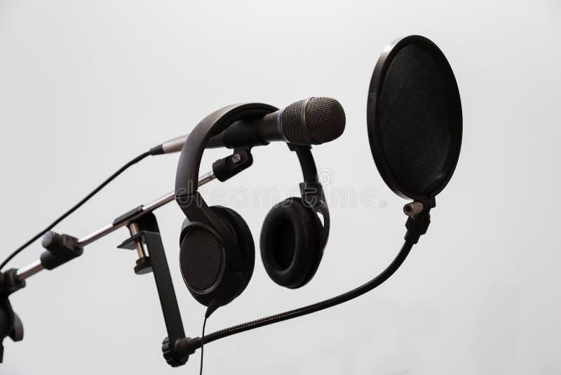 Il microfono a condensatore, le cuffie e lo schiocco cardioidi filtrano su un fondo grigio Studio di registrazione domestico immagini stock
