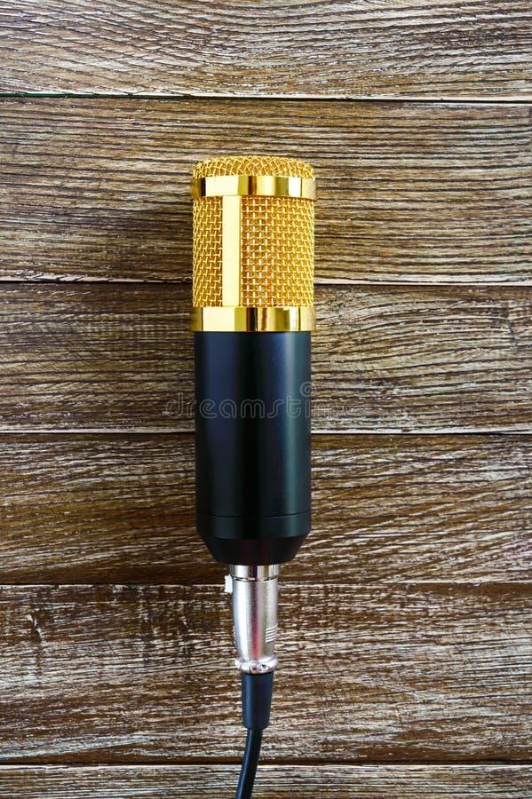 Il microfono dell'oro del condensatore si trova su una tavola di legno con lo spazio della copia Tema musicale Disposizione piana immagine stock libera da diritti