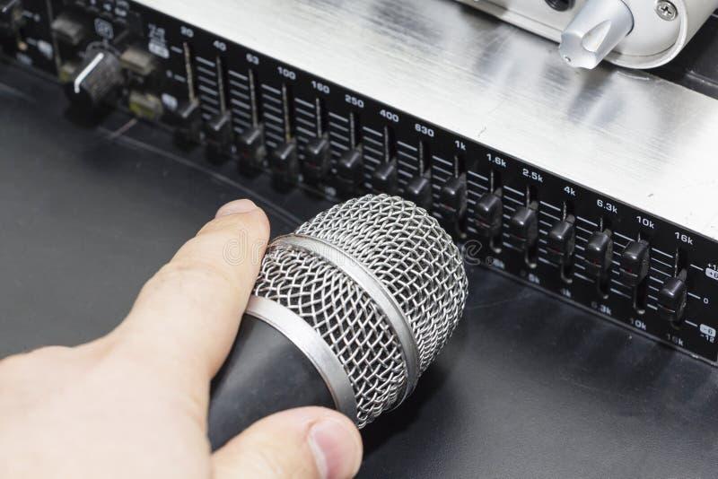 Il microfono professionale dello studio del condensatore sopra il musicista ha offuscato il fondo e l'audio miscelatore, concetto fotografia stock