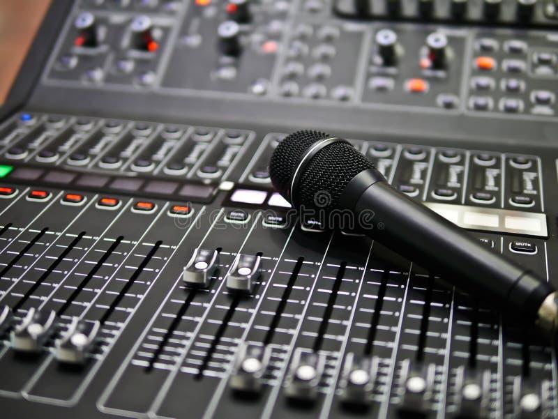Il microfono riposa su un audio regolatore del miscelatore in sala di controllo, controllo del tecnico del suono per musica in di fotografia stock