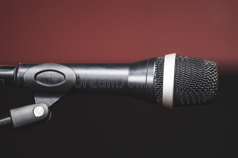 Il microfono vocale nero del primo piano ha montato sul supporto del mic, bcakground scuro rosso confuso fotografie stock