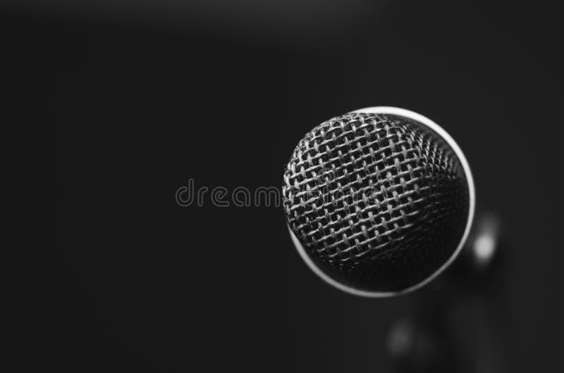 Il microfono vocale nero del primo piano ha montato sul supporto del mic, bcakground scuro rosso confuso fotografia stock