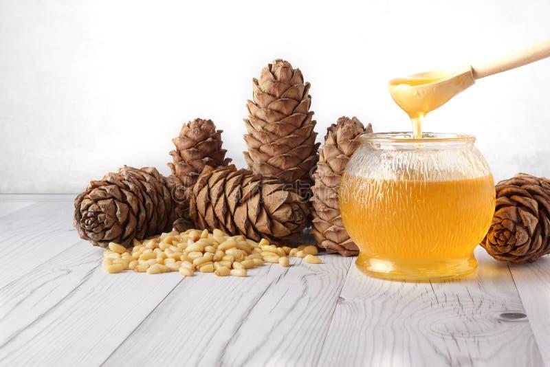 Il miele è versato da un cucchiaio di legno in un barilotto di vetro, accanto ai coni del cedro ed ai dadi su un fondo leggero immagine stock libera da diritti