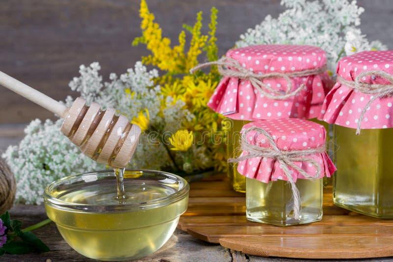 Il miele in un vetro stona e merlo acquaiolo del miele fotografia stock