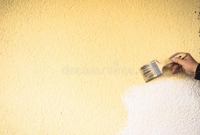 Il miglioramento domestico, mano maschio sta dipingendo la parete immagini stock libere da diritti