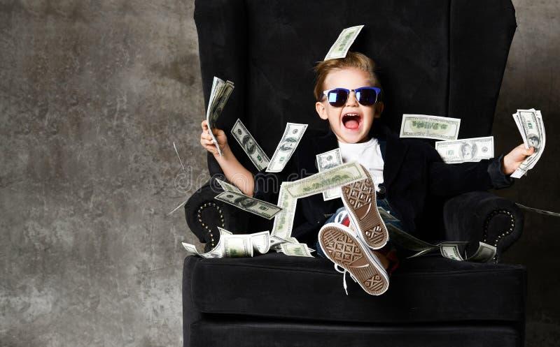 Il milionario ricco felice del ragazzo del bambino si siede in poltrona di lusso con i pacchi dei dollari incassa le sue mani nel immagini stock libere da diritti