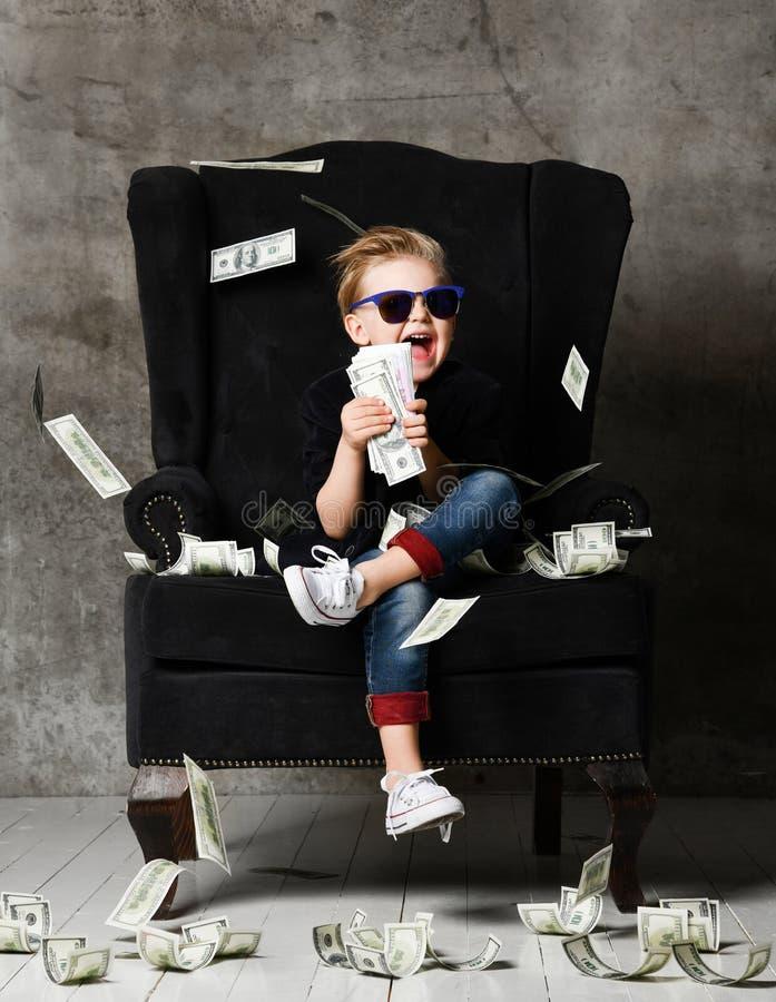 Il milionario ricco felice e shoutting del ragazzo del bambino si siede con un pacco dei dollari dei soldi incassa la grande polt immagine stock