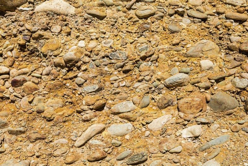 Il minerale arancio della sporcizia del ciottolo macchia il fondo fotografie stock