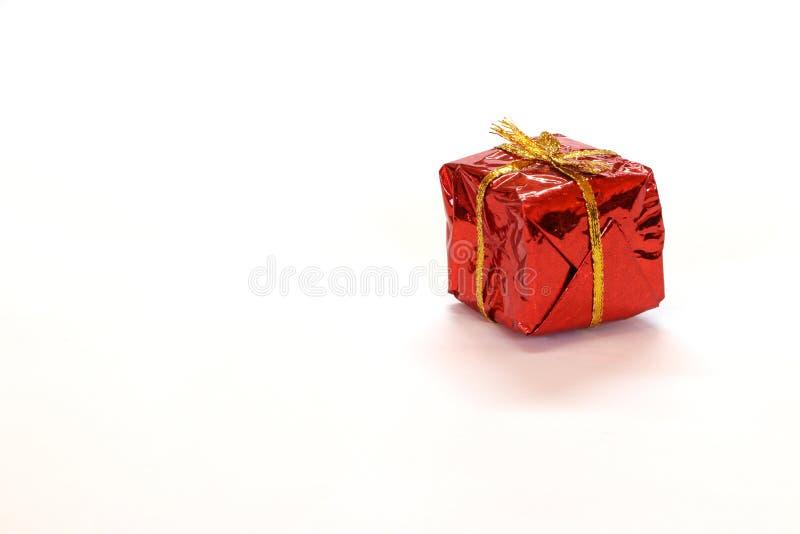 Il mini contenitore di regalo nel rosso riflette l'involucro di regalo con il nodo dorato della corda isolato su fondo bianco immagine stock